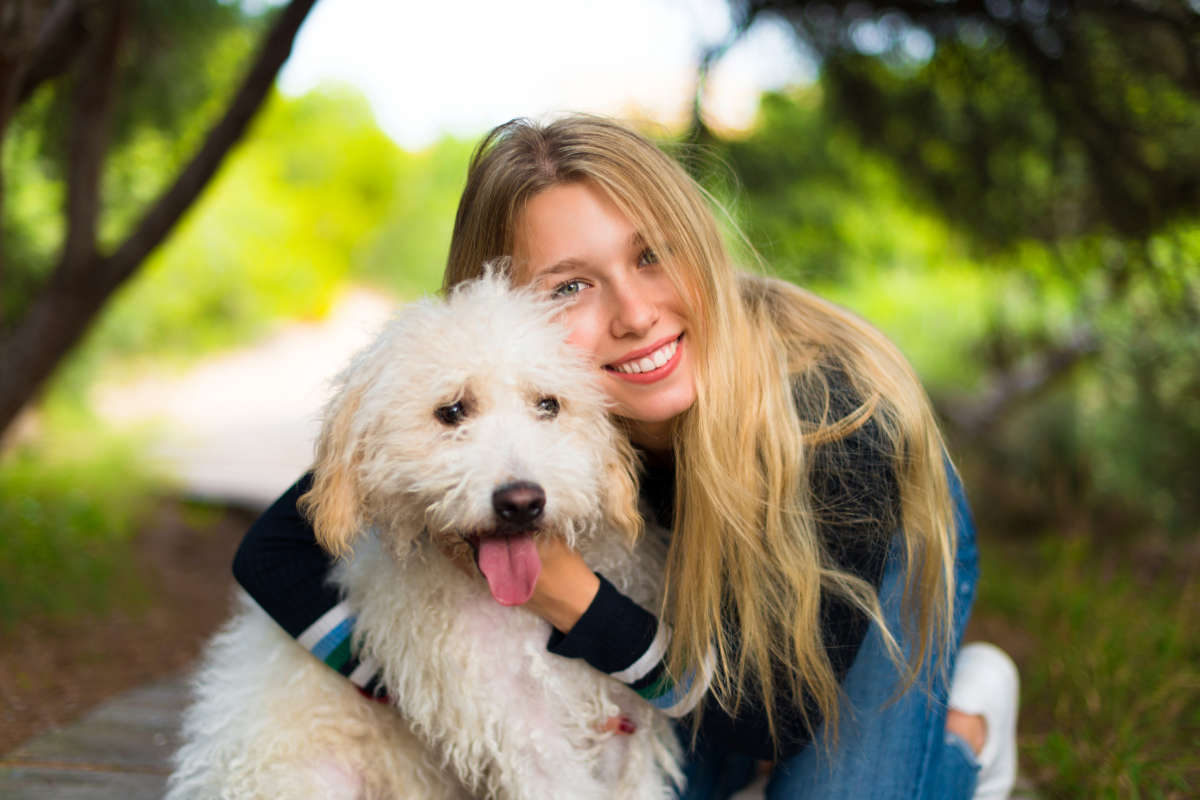 A dog owner hugs her pup (Photo: Adobe Stock)