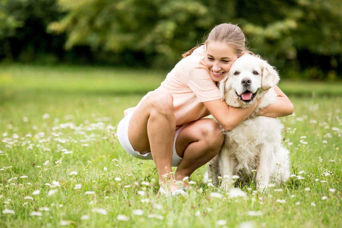 Dog owner hugs her Golden Retriever puppy (Photo: Adobe Stock)