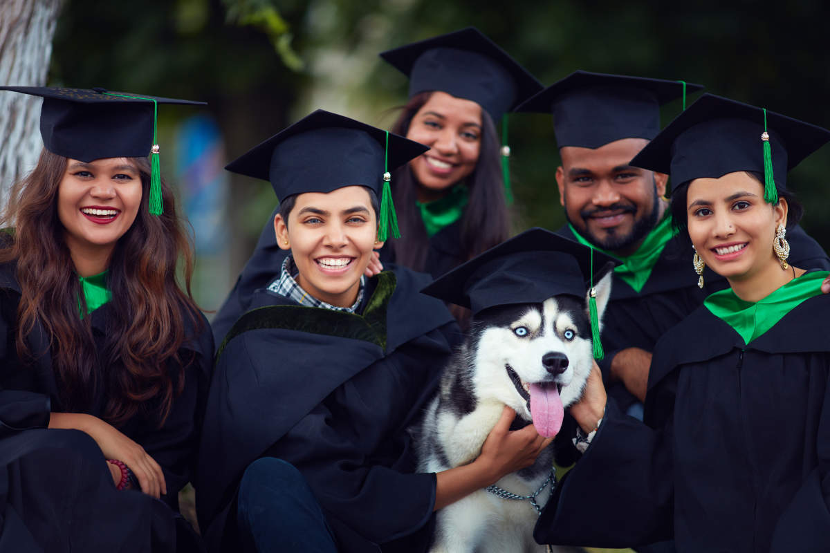 Graduates pose with a special friend at ceremony (Photo: Adobe Stock)